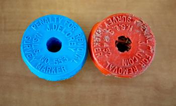 Eine neue (blau) und eine alte (orange) Vermessungsmarkierung